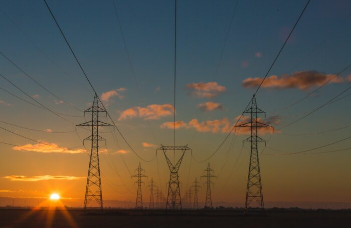 Electricity pylons against sunset
