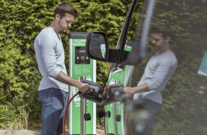 Man plugging in electric car