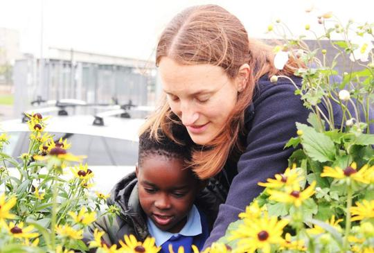 Woman and young girl look at yellow flowers