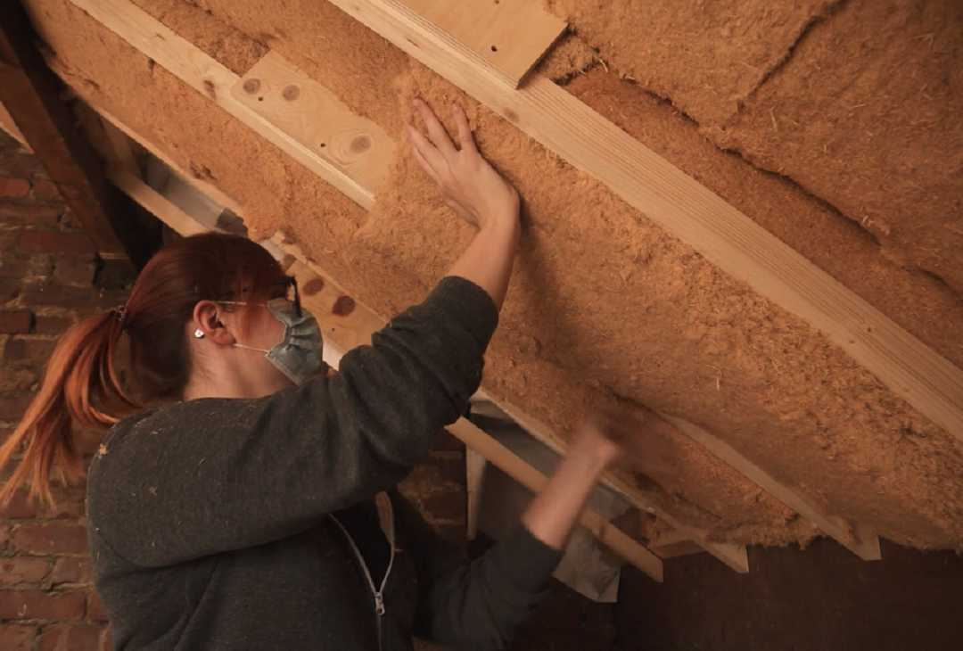 Woman installing roof insulation
