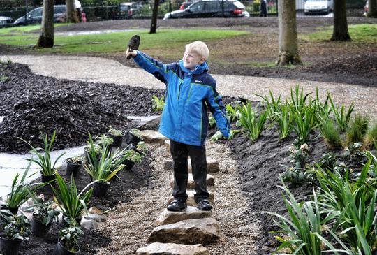 Boy holding trowel in air